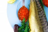 diet food - red caviar and smoked mackerel fish with lemon and dill on blue plate isolated over whit