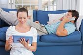 Concentrated young couple using digital tablet and cellphone in the living room at home