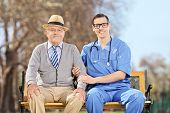 Doctor and an elderly gentleman sitting outdoors