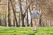 Senior gentleman walking with crutches in park