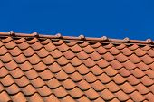 foto of red roof tile  - Red roof tile pattern over blue sky - JPG