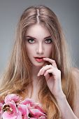 Beautiful girl, isolated on a light - grey background with pink orchids , emotions, cosmetics