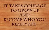 It takes courage to grow up and become who you really are - quote by E.E. Cummings on wooden red oak