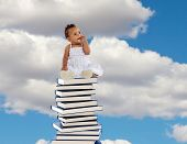 African girl sitting on a high stack of books with blue sky of background