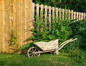 image of planters  - Decorative wooden wheelbarrow planter near wooden fence - JPG