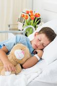 Sick little boy with teddy bear sleeping in hospital bed