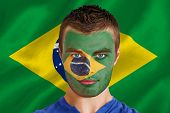 Composite image of serious young brasil fan with facepaint against digitally generated brazilian nat