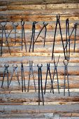 foto of blacksmith shop  - Blacksmith tools displayed on a wall indoors.