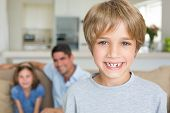 Portrait of cute boy smiling with family in background at home