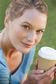 Pretty young woman holding a coffee cup outside in the park