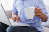 Man sitting on couch using laptop having coffee at home in the living room