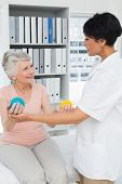 Female doctor with senior patient using stress buster balls at the medical office
