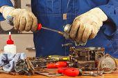 picture of carburetor  - Repairman repairing parts of the engine in the workshop  - JPG