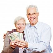 Couple of two happy senior people holding dollar bills in their hands