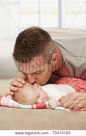 Father kissing sleeping baby tenderly.