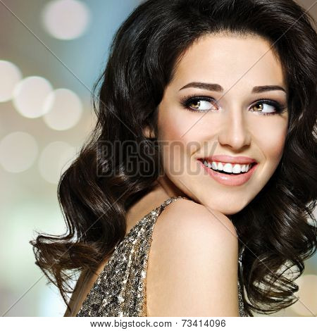 Portrait of the beautiful young happy laughing woman with brown curly hairs looking away. Pretty fashion model with dark eye makeup