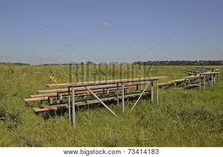 Empty bleachers surround weedy field