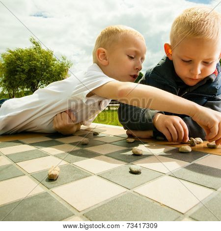 Children Playing Draughts Or Checkers Board Game Outdoor