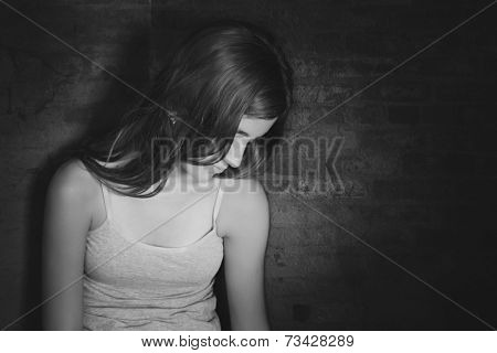 Serious and sad teenage girl sitting on the floor on black and white
