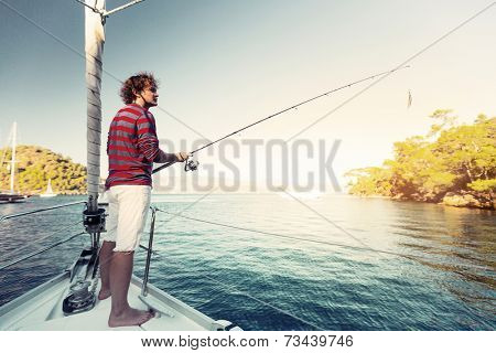 Young man fishing from the sail boat