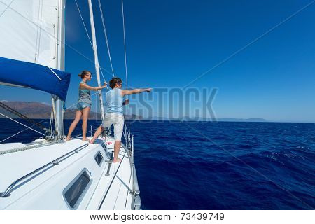 Young couple sailing in Mediterranean sea at sunny day