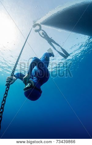 Free diver descending along the metal chain using his hands (free immersion)