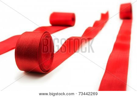 Unrolling red ribbons. Many red ribbons unrolling in multiple directions. isolated on white.