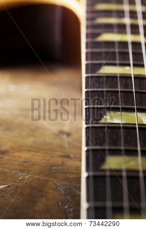 Neck and strings of an old electric guitar. Shallow depth of field.