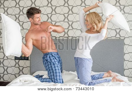 Playful attractive young couple having a pillow fight as they kneel on their bed in their sleepwear smiling and laughing