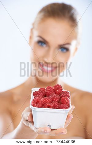 Cheerful young woman showing a plastic container full of fresh and nutritious raspberries  natural source of vitamin C and dietary fiber