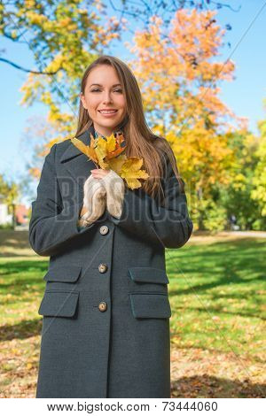 Fashionable young woman in a warm overcoat enjoying an autumn walk in a park holding a bunch of yellow leaves in her hand as she smiles at the camera