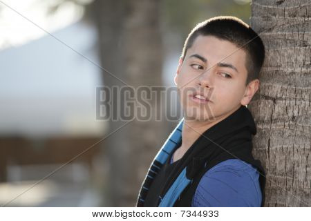 Young man leaning on a tree