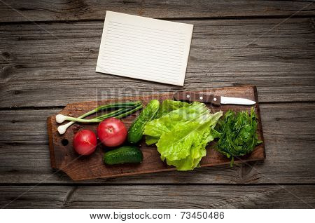 Close up of various colorful raw vegetables with paper sheet.