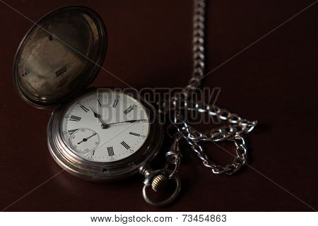 Old pocket watch on top of a wooden box