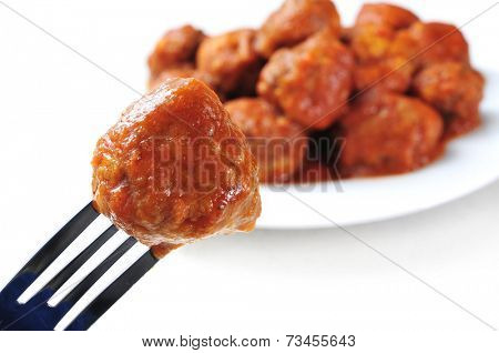 a meatball in a fork and a plate with a spanish meatballs stew on a white background