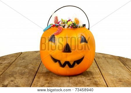 Plastic pumpkin filled with candy wooden table
