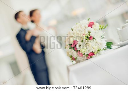 Wedding bouquet with the wedding couple in the background