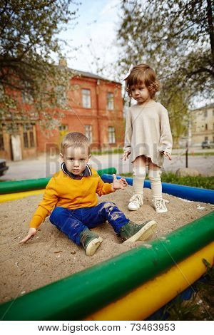 boy and girl playing in sandbox