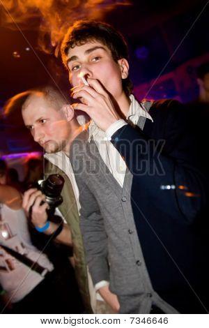 Young Man Smoking In The Nightclub