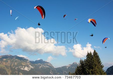 Group Of Paragliders In Mountainous Landscape