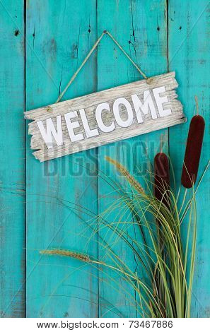 Old welcome sign hanging on antique teal blue wooden fence with cattails border