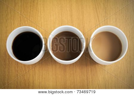 Coffee cups filled with coffee with different amounts of milk