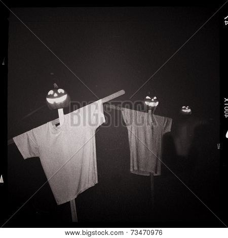 Instagram filter image of halloween scarecrows at night
