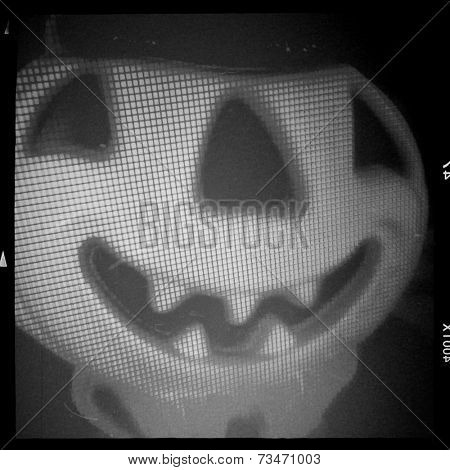 Instagram filter image of a vintage Halloween jack o lantern behind a window screen