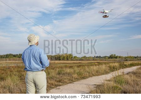 FORT COLLINS, CO, SEPTEMBER 28, 2014:  A photographer is  flying DJI Phantom 2 quadcopter with a camera above natural swamp area.