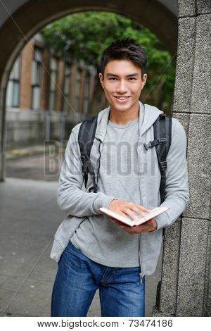 Happy smiling college student holding book at college