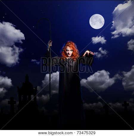 Young witch on night sky background