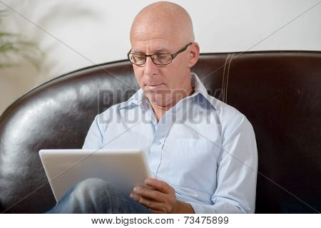 A Senior With Glasses Looks At A Digital Tablet