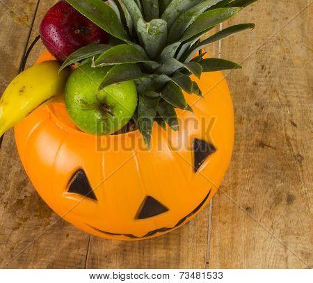 Healthy Halloween plastic pumpkin full of fruits