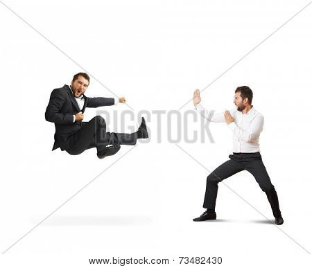 conflict between two young businessmen. one man in suit is kicking, second man standing in karate pose. isolated on white background